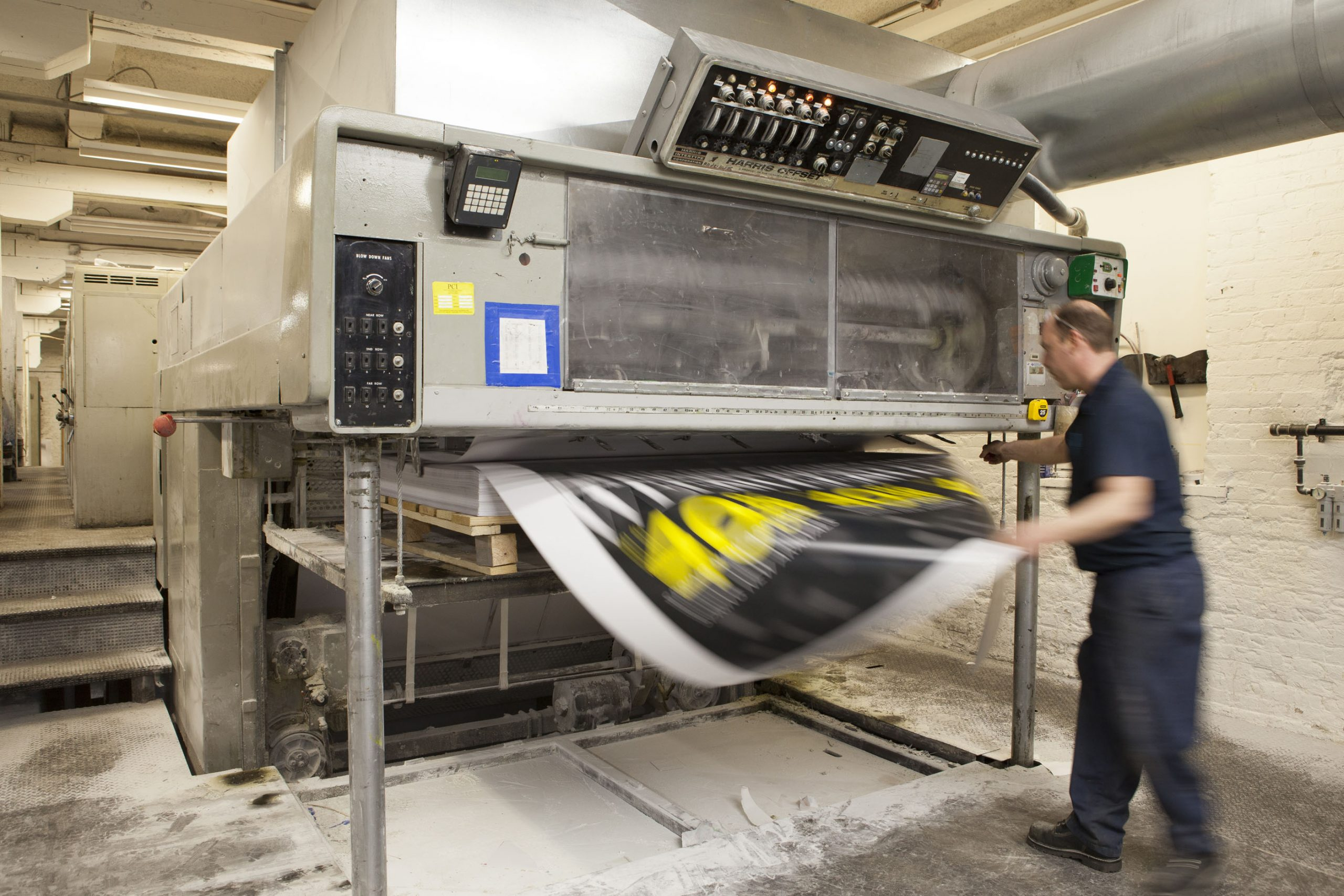 A photo of an employee holding a poster that is coming out of the printing machine.