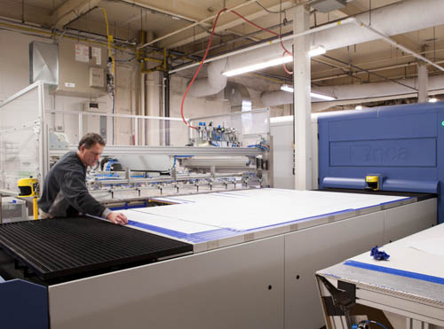 A photograph on a Brant InStore employee at the digital printing station processing a digital based image