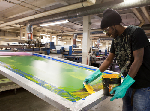 A photograph of a Brant InStore employee applying ink during the screen printing process.