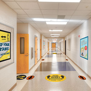 A photograph of the inside of a school hallway with social distance reminders on the floor