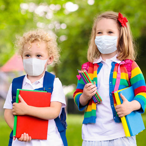 A photograph of two kids wearing masks holding books and pencil crayons ready to go to daycare