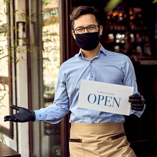 """A photograph of a restaurant employee wearing a mask and holding a """"come on in we're open"""" sign"""
