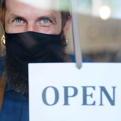 """A photograph of a retail employee wearing a mask and holding an """"open"""" sign through a window"""