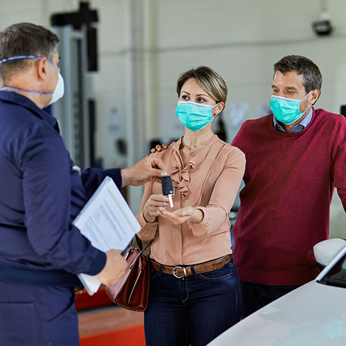 A photograph of a couple receiving car keys from a mechanic